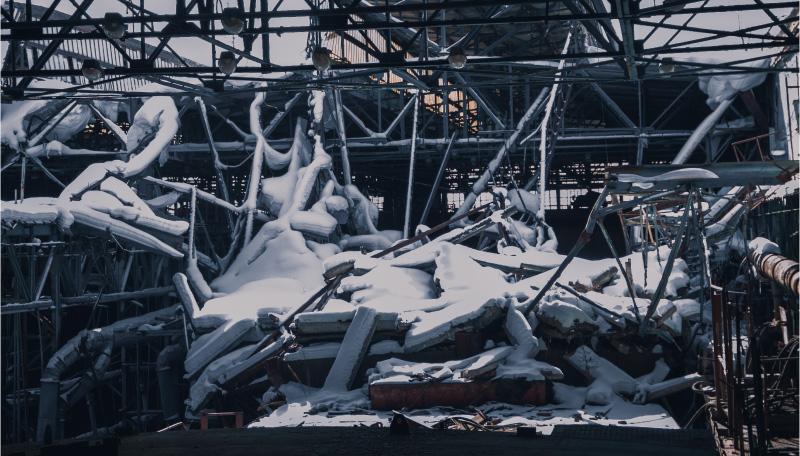 Imagen de una vieja fábrica con el tejado hundido por el peso de la nieve