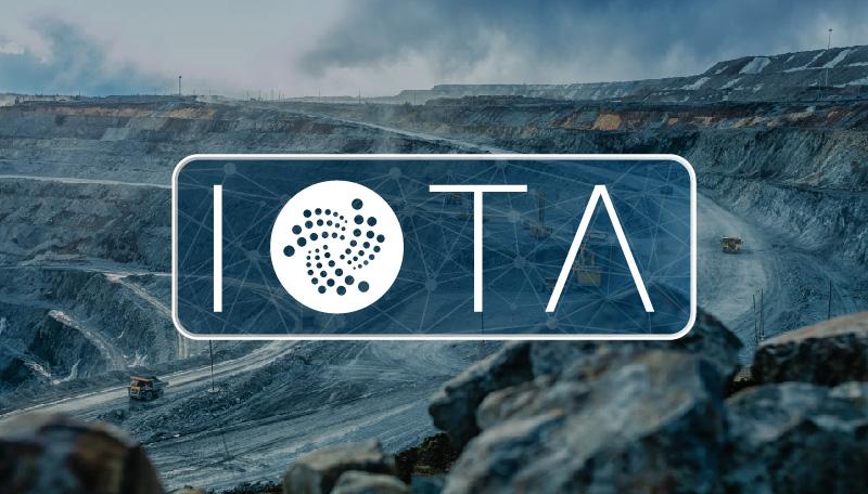 Logo de IOTA sobre la fotografía de una explotación minera