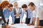 Team of employees studying blueprints at meeting